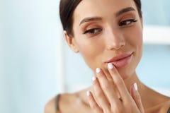 Soins de la peau de lèvres Femme avec le visage de beauté appliquant le baume à lèvres dessus photos libres de droits