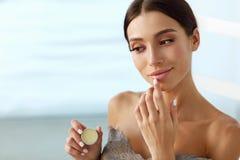 Soins de la peau de lèvres Femme avec le visage de beauté appliquant le baume à lèvres dessus Photos stock