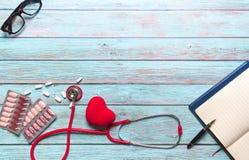 Soins de santé et stéthoscope rouge et médecine de concept médical sur le fond en bois bleu Images stock