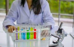 Soins de santé femelles de scientifique fonctionnant dans le laboratoire de chimie, avec les bouteilles colorées et les tubes chi images libres de droits