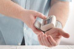 Soins de santé pour les hommes avec le moniteur de rythme et de tension artérielle Photographie stock libre de droits