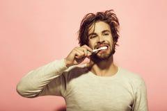 Soins dentaires de matin des dents de brosse de l'homme avec la pâte dentifrice image libre de droits