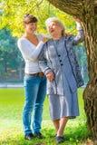 Soins et petite-fille affectueuse marchant avec sa grand-mère Photo stock