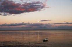 Soirée calme à l'océan avec les nuages dramatiques au coucher du soleil photographie stock