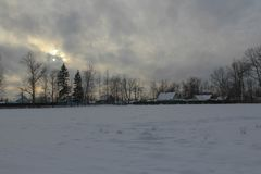 Soirée d'hiver dans le village Les ensembles du soleil, nuages, froid, obscurité de gel images stock