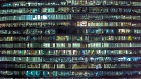 Soirée fonctionnante dans l'immeuble de bureaux en verre avec de nombreux bureaux avec le timelapse de murs de verre et de fenêtr banque de vidéos