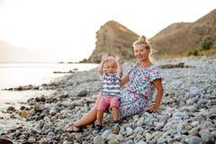 Soirée, plage de mer Le fils s'assied sur son recouvrement du ` s de mère et mange le fruit et les baies Images stock