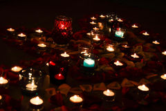 Soirée romantique par lueur d'une bougie avec des pétales de rose Photos libres de droits