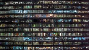 Soir?e fonctionnante dans l'immeuble de bureaux en verre avec de nombreux bureaux avec le timelapse de murs de verre et de fen?tr banque de vidéos