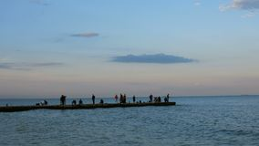 Soir?e sur la Mer Noire Les gens marchent le long du brise-lames la soirée chaude et calme d'été et admirent le coucher du soleil banque de vidéos