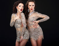 Soiree. Two Young Surprised Women over Black Royalty Free Stock Images