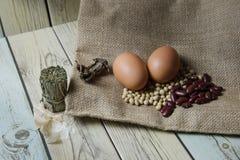 Sojabohnenöl und rote Bohnen und Ei auf den Taschen des groben Sackzeugs Stockfoto