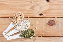 Sojabohnen, grüne Bohnen und Hirse im Löffel auf hölzernem Hintergrund Lizenzfreie Stockfotos