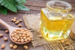 Sojabohnenölbohne und Sojabohnenölöl auf Holztisch Stockfotografie