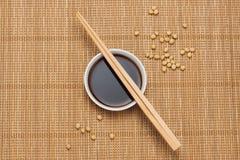 Sojasaus en sojaboon met eetstokjes op houten lijst royalty-vrije stock foto
