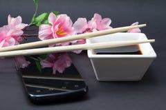 Sojasoße in einem weißen Teller und in den Essstäbchen stockfotografie