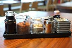 Sojasoße, gebratener Knoblauch, weißer indischer Sesam in der Glasflasche mit Paprika und Pfefferschüttel-apparat Stockbild