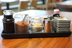 Sojasoße, gebratener Knoblauch, weißer indischer Sesam in der Glasflasche mit Paprika und Pfefferschüttel-apparat Lizenzfreies Stockbild