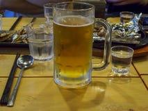 Soju-Gläser voll vom soju und ein Bierglas voll vom Bier mit koreanischen Beilagen an der Jahresabschluss- Partei in Korea lizenzfreie stockfotos