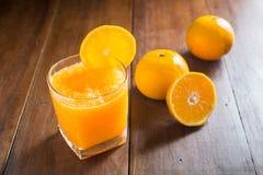 Sok pomarańczowy w szkle, świeże owoc na drewnianym tle obraz stock