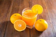 Sok pomarańczowy w szkle, świeże owoc na drewnianym tle fotografia stock