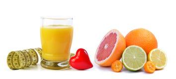 Sok pomarańczowy w szkle, taśmy miarze, sercu i cytrus owoc odizolowywać na białym tle, Fotografia Royalty Free