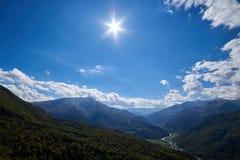 Sol över bergdalen med floden och vägen arkivfoton