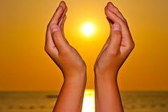 Sol över havet i händer Arkivbild