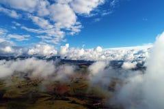 Sol över moln med en blå himmel och ett stort landskap royaltyfri foto
