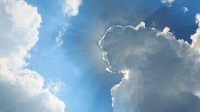 Sol bak ett fluffigt moln fotografering för bildbyråer
