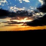 Sol bak moln ovanför landskap arkivfoto