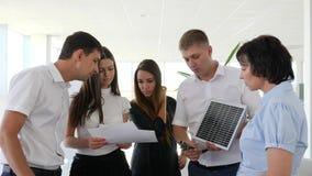 Sol- batteri in i händer av affärsmannen med kollegor i modernt kontor lager videofilmer