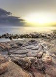 Sol brillante en la puesta del sol, iluminando la serpiente de piedra Foto de archivo