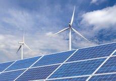 Sol- celler med vindturbiner som frambringar elektricitet i hybrid- kraftverksystemstation på bakgrund för blå himmel Royaltyfri Bild