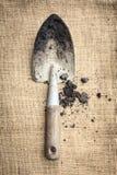 Sol d'outils de jardinage sur le fond de sac Photographie stock libre de droits