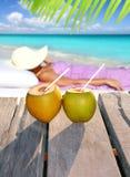 Sol da mulher dos cocos que tanning a praia tópica Imagem de Stock Royalty Free