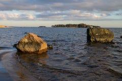 Sol da noite nas rochas da costa do oceano Fotografia de Stock
