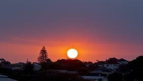 Sol de ajuste redondo vermelho sobre um subúrbio urbano Foto de Stock Royalty Free