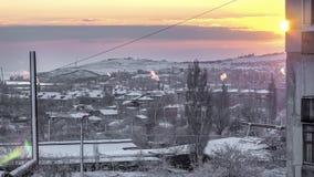 Sol de aumentação na cidade da neve e sobre a fábrica Fotos de Stock Royalty Free