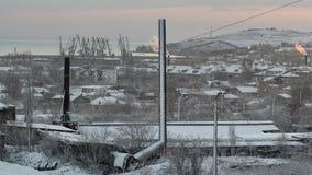 Sol de aumentação na cidade e neve sobre a fábrica imagem de stock royalty free