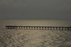 Sol de la playa que fija el embarcadero nublado del Golfo de México foto de archivo