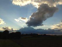 Sol de la tarde detrás de las nubes grandes hermosas sobre campos oscuros Fotos de archivo libres de regalías