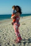 Sol del abarcamiento de la madre en la playa en fuerte viento Imagen de archivo