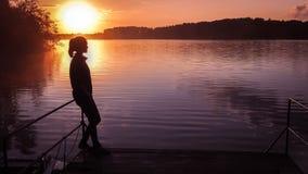Sol do fundo da menina da silhueta Menina que está a água próxima fora Lago do por do sol do ouro Jovem mulher que pensa sobre al Fotos de Stock Royalty Free
