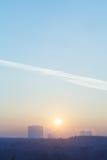 Sol do nascer do sol no céu azul sobre a cidade no inverno frio Fotografia de Stock Royalty Free