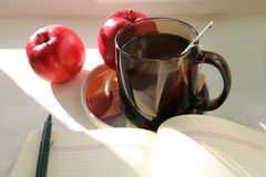 sol Dom Una taza de té refrescado, frutas, un diario abierto con una pluma Imagen de archivo libre de regalías