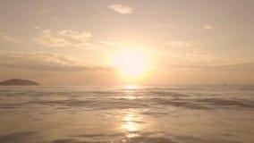 Sol dourado no céu colorido no por do sol e em espirrar ondas de água no mar, opinião do zangão Nascer do sol adiantado da paisag video estoque