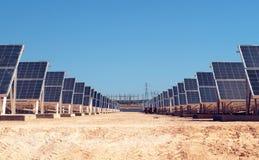 Sol- fält med elkraftstationen i bakgrunden arkivfoton