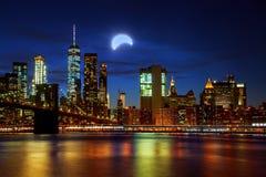 Sol- förmörkelse, New York NY august 21 2017New York City& x27; upplyst bro- och Manhattan för s Brooklyn horisont Fotografering för Bildbyråer