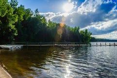 Sol-gjord genomvåt kust av skogsjön med en pir och vitfartyg på bakgrund för blå himmel Royaltyfria Bilder